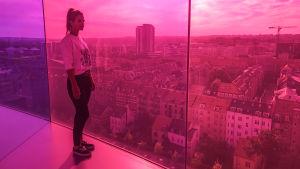 Nainen seisoo pilvenpiirtäjässä huoneessa, jonka seinät ovat lasia. Värit puna-violetti.