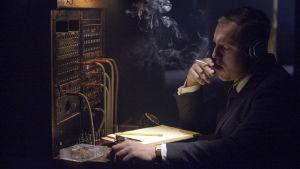 Mies puhelinvaihteen näköisessä paikassa istuu ja polttaa tupakkaa.