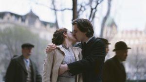 Nainen ja mies suutelevat toisiaan keskellä katunäkymää.
