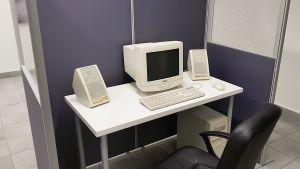 Bild på Nayab Ikrams konstverk som är ett kontorslandskap med tillhörande kontorsmöbler samt en stor dator av äldre modell.