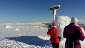 Två skidåkare i rött och lila står på toppen av ett fäll i Lappland och tar foton.