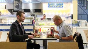 Kaksi miestä pikaruokaravintolassa syömässä.