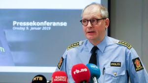 Tommy Brøske, en norsk polis, framför en drös mikrofoner.