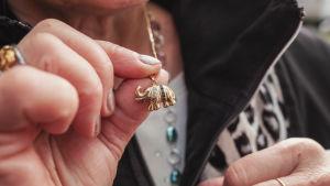 Naisen esittelee lähikuvassa kultaista norsukaulariipustaan.