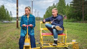 Egenlandin juontajat Hannamari Hoikkala ja Nicke Aldén ajavat resiinalla Suolahden rautatiemuseon huoltoraiteella. Hoikkala ajaa, Aldén istuu kyydissä.