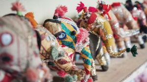 Erivärisiä tekstiilisiä norsuja rivissä hyllyllä.