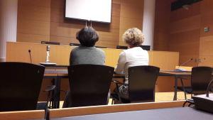 Två kvinnor fotograferade bakifrån i rättssalen.