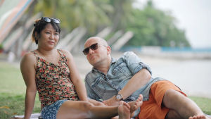 Nainen ja mies rannalla. Nainen istuu, mies makaa kyljellään kyynärpäähänsä nojaten ja katsoo naista.
