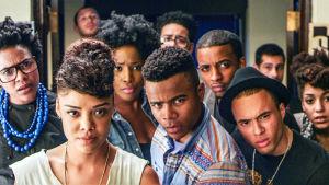 Ryhmä tummaihoisia nuoria aikuisia katsoo kameraan kysyvästi.