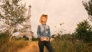 Dokumentin ohjaaja poseeraa cowboyhatussa pellolla taustalla feikki Eiffeltorni