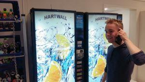 Gymnasieeleven Rasmus Östdahl står med telefon i hand och beställer läsk från en varuautomat i skolan.