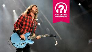Dave Grohl spelar på en elgitarr och ler brett med öppen mun.