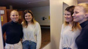 Emmy Wikström i blå skjorta och Antonia Holmgren i vit skjorta syns dubbelt i en spegel.