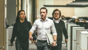 Nainen ja kaksi miestä kävelevät toimistokäytävällä huolestuneen ja vauhdikkaan näköisesti.