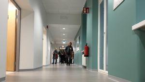 Människor i en korridor med grått golv och turkosa väggar.