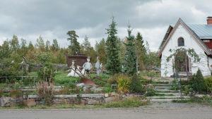 Pieni valkoinen kivikirkko ja puutarha, jossa on patsaita ja Nooan arkki tien vieressä.