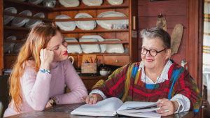 Kaksi naista selailee leikekirjaa pöydän ääressä vanhan hirsitalon tuvassa.