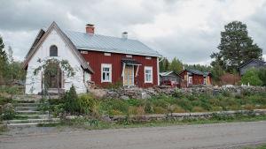 Valkoinen pieni kivikirkko tien reunassa, takana punainen vanha hirsitalo ja muita rakennuksia.