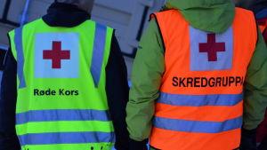 Två personer står med ryggen mot kameran. Den ena har en gul Röda Korset-väst. Den andra en röd väst där det står skredgruppen.