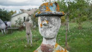 Veistos, joka esittää ihmistä ja jolla on silmälasit ja lierihattu päässään puutarhassa. Taustalla muita patsaita.
