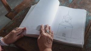 Kädet, jotka selailevat leikekirjaa pöydällä. Kirjassa kuva kirkon rakennuspiirustuksesta.