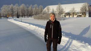 Lilja Öhman, en ljushårig dam, står i snön framför en idrottshall.