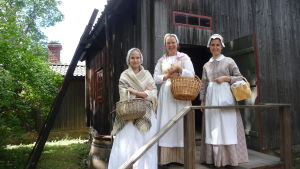 Tre kvinnor står utanför en museistuga på Klosterbacken.