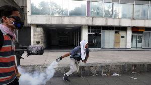 En demonstrant i Venezuela kastar en rökgranat.