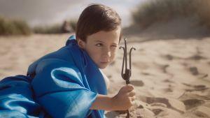 Aatos ligger på stranden och leker Poseidon. Stillbild ur dokumentären Aatos ja Amine.