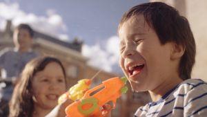 Aatos och Saimi leker med vattenpistoler. Stillbild ur dokumentären Aatos Amine.