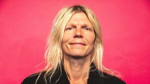 Jori Sjöroos hymyilee kameralle lähikuvassa pinkin taustan edessä.