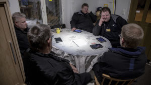 Tor-Erik Stolpe sitter med fyra andra taxichaufförer vid ett köksbord i chaufförernas lokal på Norra Strandgatan i Ekenäs.