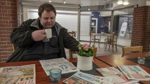 Taxichauffören Tor-Erik Stolpe sitter vid ett bord inne i en grillkiosk och dricker kaffe medan han läser tidningen.