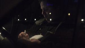 Taxichauffören Tor-Erik Stolpe sitter i bilen i mörkret och antecknar.