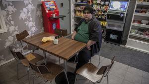 Tor-Erik Stolpe sitter vid ett bord i Österby kiosk i Ekenäs.