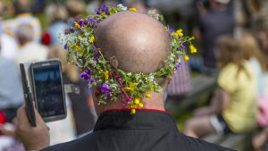 En man som har en blomkrans på huvudet och han håller i en mobiltelefon.