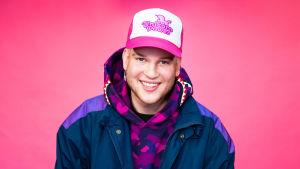 Lippalakkipäinen Lukas Leon hymyilee pinkin taustan edessä.