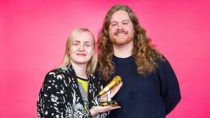 YleX Läpimurto -voittaja Ruusut-yhtyeen Ringa Manner ja Alpo Nummelin pitelevät kultaista mikrofonia ja hymyilevät pinkin taustan edessä.