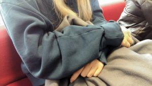 En flicka sitter med armarna i kors i en soffa, man ser inte hennes ansikte.
