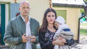Martin och Sima med bebis i famnen utanför sitt hus.