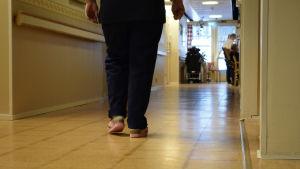 Två ben som går bortåt i en korridor i Almahemmet.