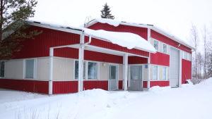 Ett rött hus med en stor lagerbyggnad intill.