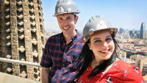 Nainen ja mies seisovat rakennustyömaakypärät päässä jonkin korkean rakennuksen terassilla.