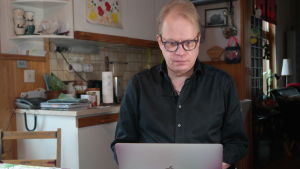 Författaren Peter Sandström siier och jobba vid sin dator vid sitt köksbord