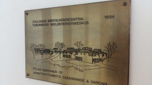 En mässingsskylt med en bild av och text om att Åbolands mentalvårdscentral är byggd 1994.