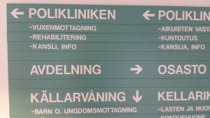 Gröna skyltar med som visar vart man ska gå för att komma till polikliniken, avdelning eller källarvåning på en psykiatrsik mottagning-.