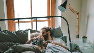 Nainen ja mies halaavat peiton alla sängyssä.