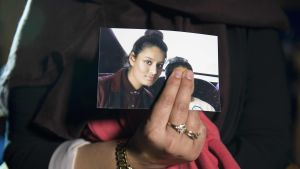En person håller upp ett fotografi på Shemima Begum.