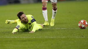 Lionel Messi biter i gräset.