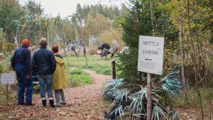 Kolme ihmistä seisoo aukean laidalla, etualalla kyltti, jossa lukee 'näyttely'.